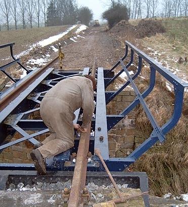 Zum Schluss wurden die Schienen mit den oben erwähnten Passschrauben am Brückenträger befestigt.  Im Hintergrund sieht man schon die planierte Trasse.